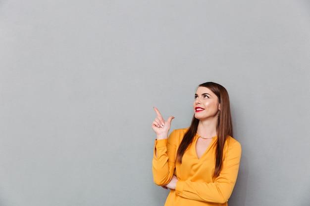 Portret van een gelukkige vrouw die vinger benadrukt Gratis Foto