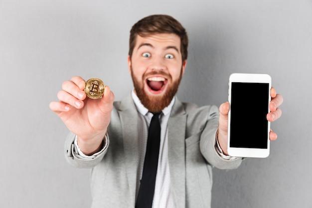 Portret van een gelukkige zakenman die bitcoin houdt Gratis Foto