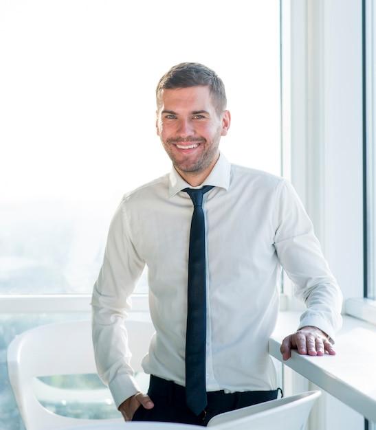 Portret van een gelukkige zakenman die zich in bureau bevindt Gratis Foto