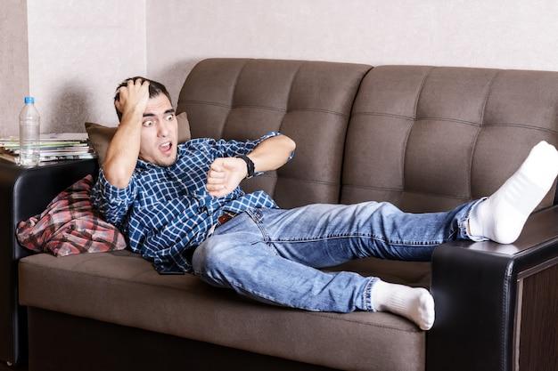 Portret van een geschokte man, wakker op de bank thuis en kijkt op zijn horloge, geslapen op het werk Premium Foto