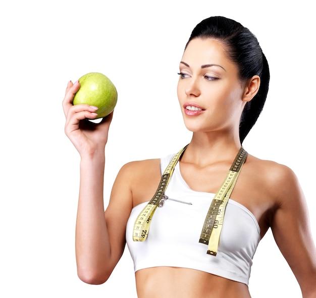 Portret van een gezonde vrouw met appel en een fles water. gezond fitness- en eetlevensstijlconcept. Gratis Foto