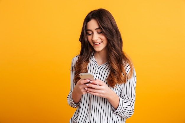 Portret van een glimlachend jong meisje die mobiele telefoon met behulp van Gratis Foto