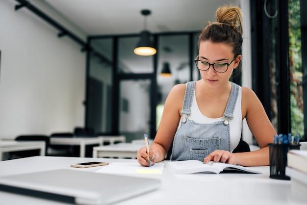 Portret van een glimlachend millenial meisje die nota's van handboek maken. Premium Foto