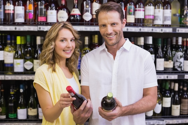 Portret van een glimlachend toevallig paar dat wijnfles bekijkt Premium Foto