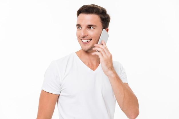 Portret van een glimlachende aantrekkelijke man in wit t-shirt Gratis Foto
