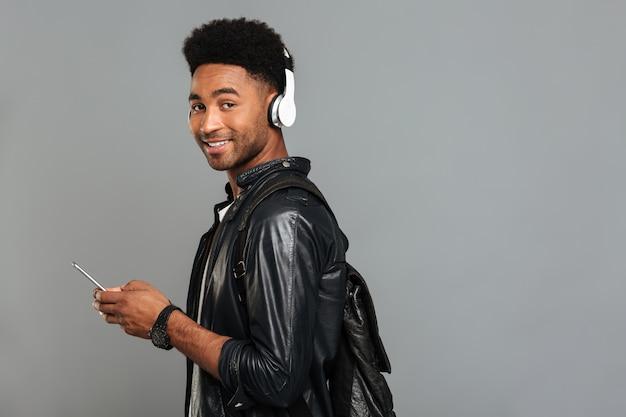 Portret van een glimlachende afro-amerikaanse man met rugzak Gratis Foto