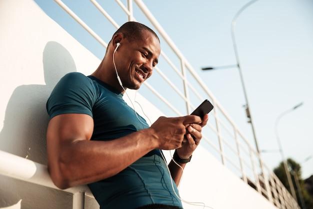 Portret van een glimlachende afro amerikaanse sportman die aan muziek luistert Gratis Foto