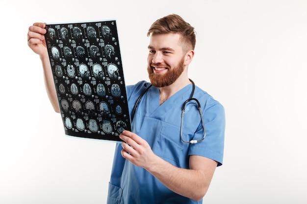 Portret van een glimlachende arts die ct aftasten bekijkt Gratis Foto