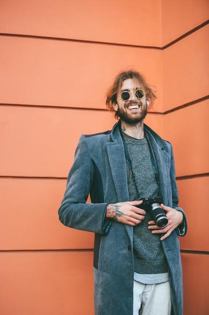 Portret van een glimlachende bebaarde man met vintage camera Gratis Foto