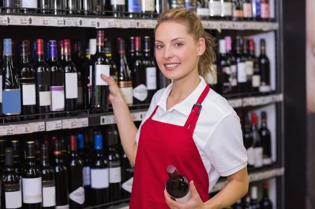 Portret van een glimlachende blonde arbeider die een wijnfles neemt Premium Foto