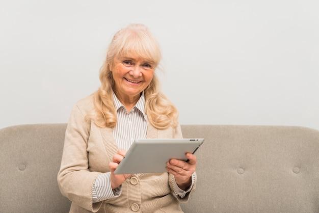Portret van een glimlachende blonde hogere vrouw die digitale tablet in hand houdt bekijkend elkaar Gratis Foto
