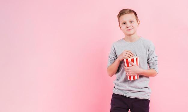 Portret van een glimlachende de popcornemmer van de jongensholding tegen roze achtergrond Gratis Foto