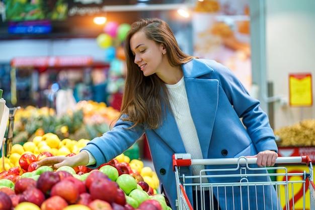Portret van een glimlachende gelukkig aantrekkelijke jonge vrouw koper met kar in de supermarkt supermarkt tijdens het kiezen en kopen van verse appels op fruit afdeling Premium Foto