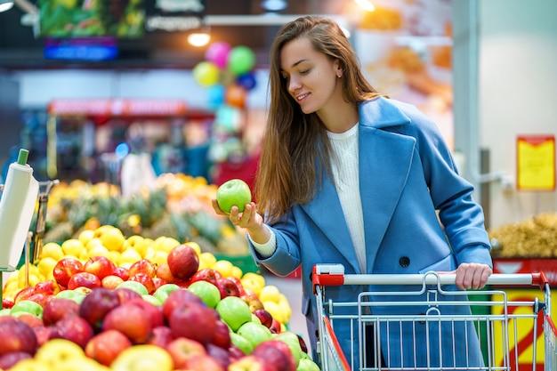 Portret van een glimlachende gelukkige aantrekkelijke jonge vrouwenkoper met kar in de kruidenierswinkelopslag tijdens het kiezen van verse appelen terwijl het kopen van vruchten Premium Foto