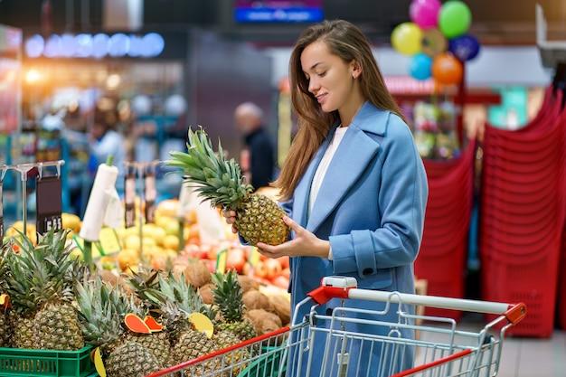 Portret van een glimlachende gelukkige aantrekkelijke vrouwenkoper met kar in de kruidenierswinkelopslag tijdens het kiezen van en het kopen van verse ananas bij fruitafdeling Premium Foto