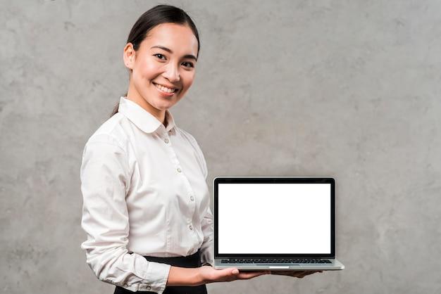Portret van een glimlachende jonge aziatische zakenman die laptop met witte het schermvertoning toont Gratis Foto