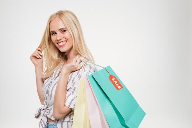 Portret van een glimlachende jonge blonde vrouw met boodschappentas Gratis Foto
