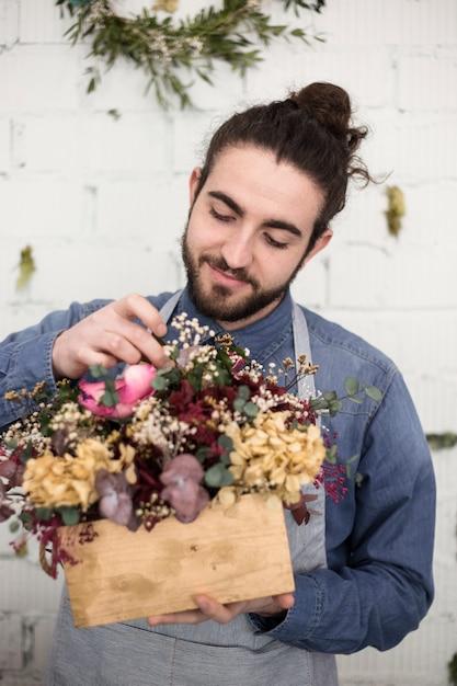 Portret van een glimlachende jonge mannelijke bloemist die de bloemen in de houten doos schikken Gratis Foto