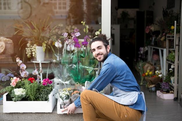 Portret van een glimlachende jonge mannelijke bloemist die de bloemen in de krat schikken Gratis Foto