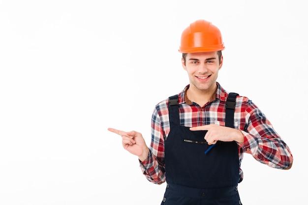 Portret van een glimlachende jonge mannelijke bouwer wijzen Gratis Foto