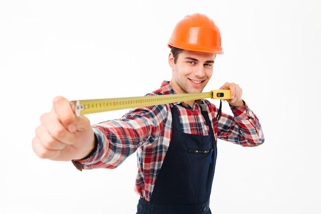 Portret van een glimlachende jonge mannelijke bouwer Gratis Foto