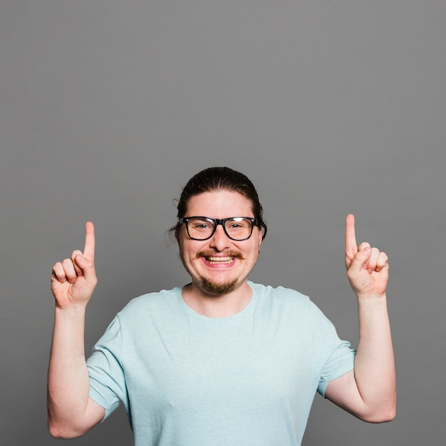 Portret van een glimlachende jonge mens die vingers richten die omhoog camera bekijken Gratis Foto