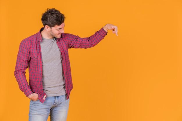 Portret van een glimlachende jonge mens die zijn vinger naar beneden op een oranje achtergrond richt Gratis Foto