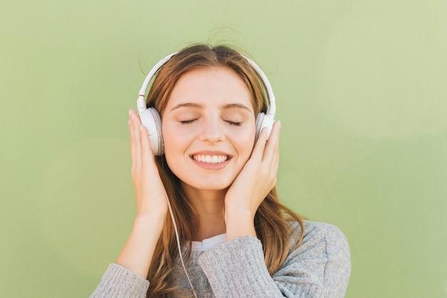 Portret van een glimlachende jonge vrouw die de muziek op hoofdtelefoon met haar oog luistert dat tegen munt groene achtergrond wordt gesloten Gratis Foto