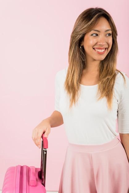 Portret van een glimlachende jonge vrouw die zich dichtbij de bagagezak tegen roze achtergrond bevindt Gratis Foto