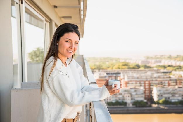 Portret van een glimlachende jonge vrouw die zich in balkon bevindt dat witte koffiekop houdt Gratis Foto