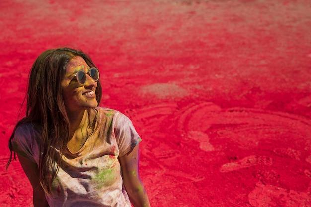 Portret van een glimlachende jonge vrouw die zonnebril draagt die in holikleur knoeien Gratis Foto