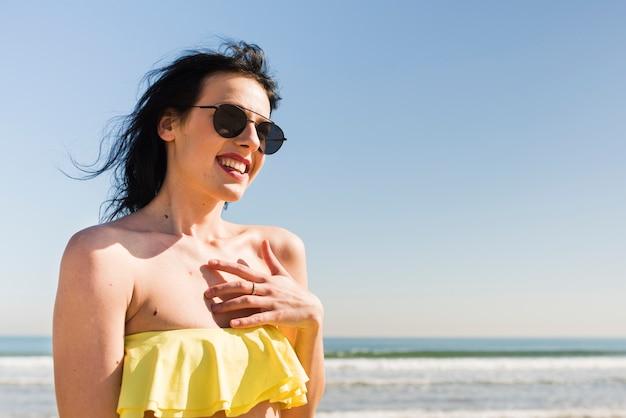 Portret van een glimlachende jonge vrouw in bikinitop die zich tegen blauwe hemel bij strand bevindt Gratis Foto