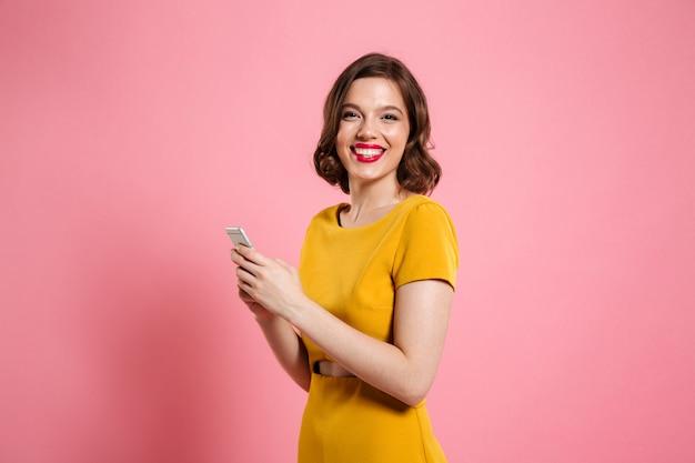 Portret van een glimlachende jonge vrouw in jurk Gratis Foto