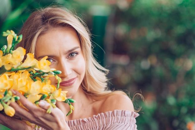 Portret van een glimlachende jonge vrouw wat betreft de gele fresiabloemen zorvuldig Gratis Foto