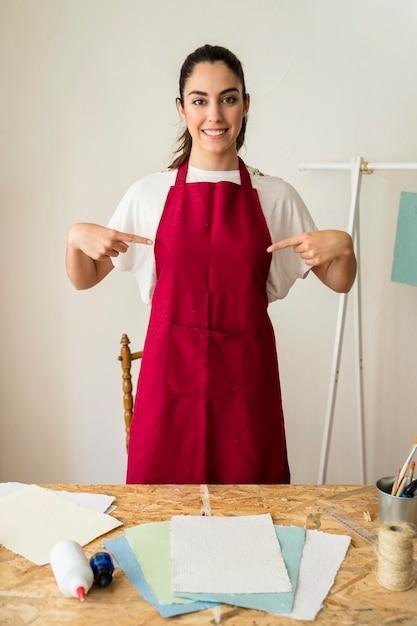 Portret van een glimlachende jonge vrouw wijzende vingers op haar rode schort Gratis Foto