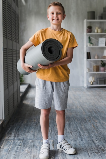 Portret van een glimlachende jongen die grijs opgerolde oefeningsmat ter beschikking houdt Gratis Foto