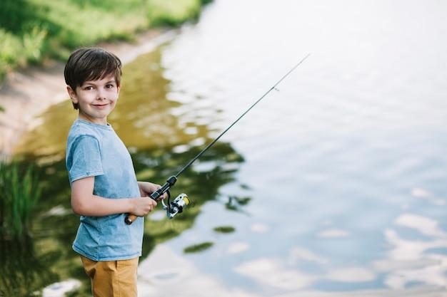 Portret van een glimlachende jongen die op meer vissen Gratis Foto