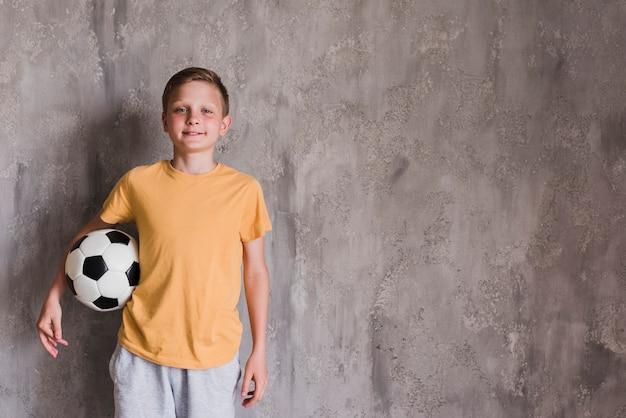 Portret van een glimlachende jongen met voetbalbal die zich voor concrete muur bevinden Gratis Foto