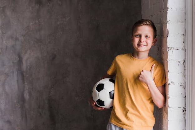 Portret van een glimlachende jongen voor het concrete het bal van de muurholding voetbal tonen beduimelt omhoog Gratis Foto