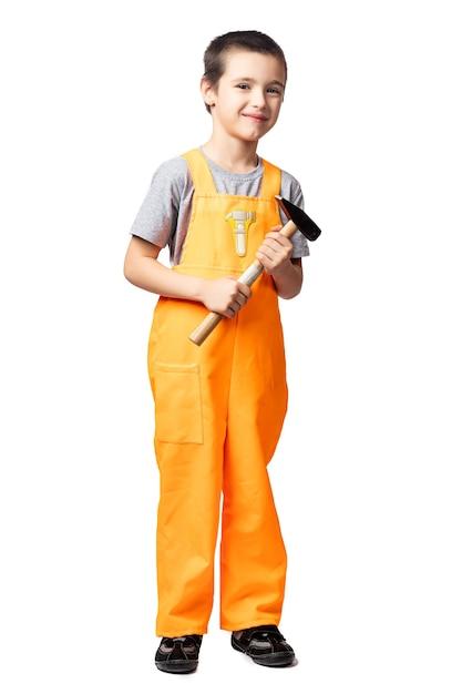 Portret van een glimlachende jongenstimmerman in oranje werkoveralls die een hamer in zijn handen houden Premium Foto