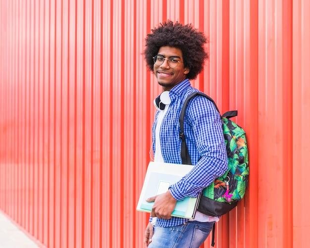 Portret van een glimlachende mannelijke studenten dragende zak op schouder en boeken die in hand aan camera kijken Gratis Foto