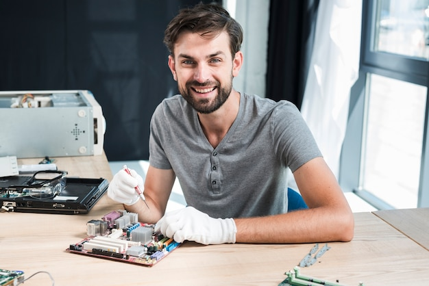 Portret van een glimlachende mannelijke technicus die aan computermotherboard werkt Gratis Foto