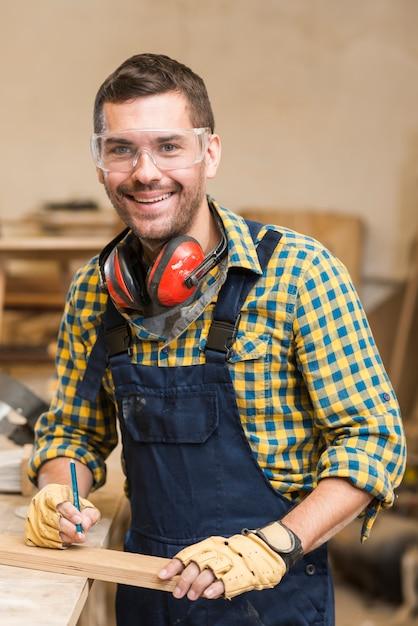Portret van een glimlachende mannelijke timmerman die houten plank en potlood houdt Gratis Foto
