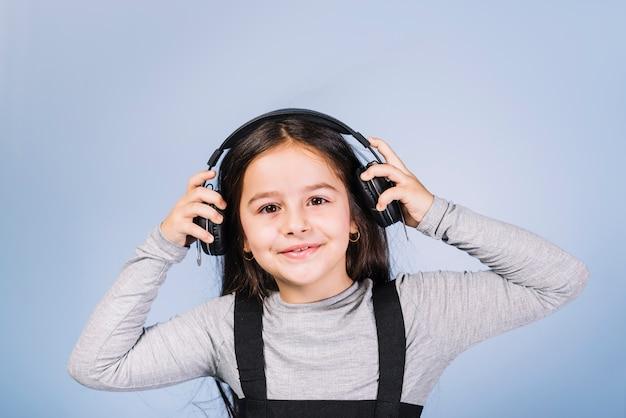 Portret van een glimlachende meisje het luisteren muziek op hoofdtelefoon tegen blauwe achtergrond Gratis Foto
