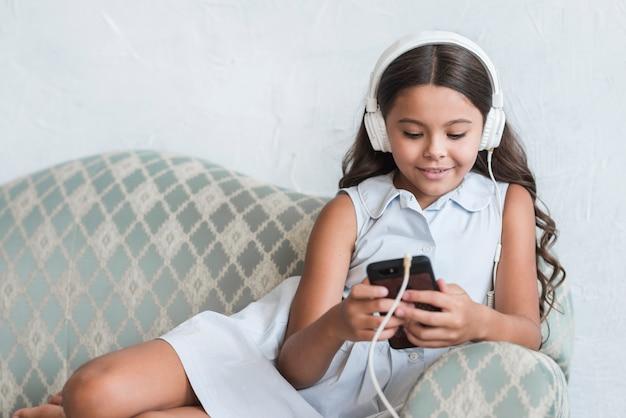 Portret van een glimlachende meisjeszitting op bank die mobiele telefoon met hoofdtelefoon op haar hoofd met behulp van Gratis Foto