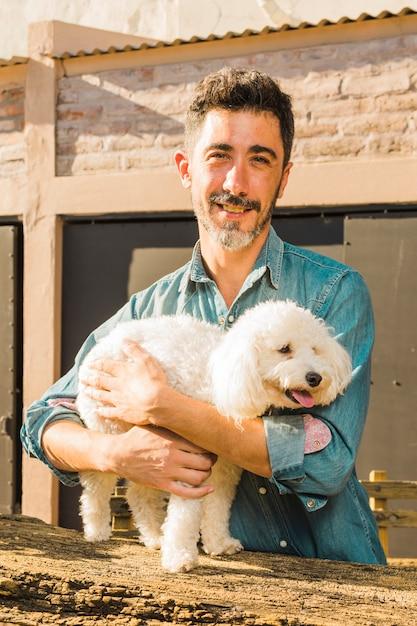 Portret van een glimlachende mens die zijn witte hond koestert Gratis Foto