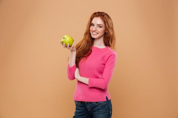 Portret van een glimlachende mooie de holdingsappel van het roodharigemeisje Gratis Foto