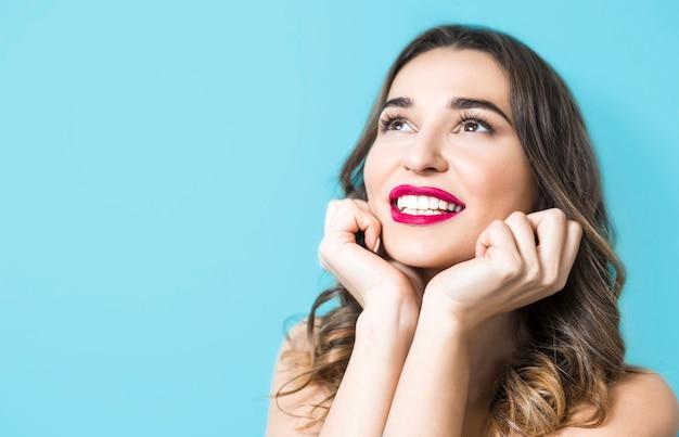 Portret van een glimlachende mooie jonge vrouw, gezonde witte tanden. gezichtsmeisje met rode lippenstift. Premium Foto
