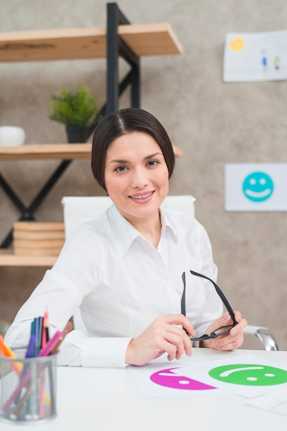 Portret van een glimlachende mooie vrouwelijke psycholoog die zwarte oogglazen in hand houdt Gratis Foto