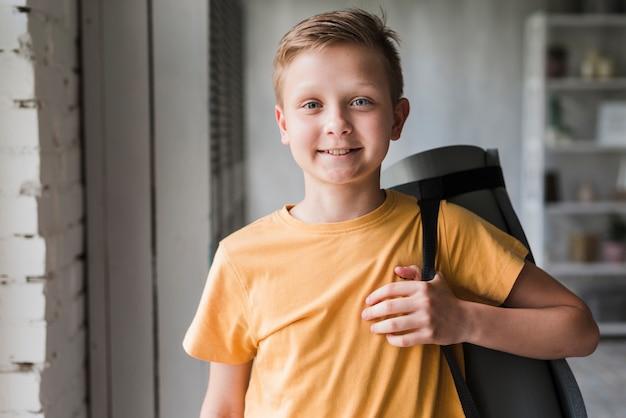 Portret van een glimlachende oefeningsmat van de jongensholding op zijn schouder Gratis Foto